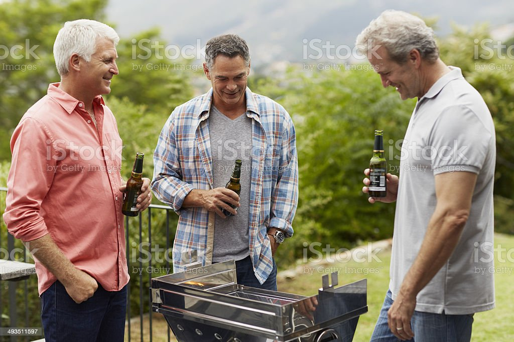 Mature friends having beer while barbecuing​​​ foto