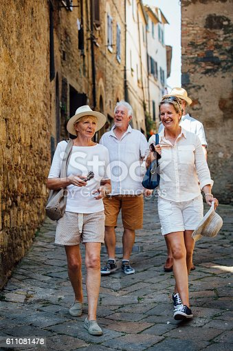 Mature couples looking around old town Italy. They walk down a narrow street while on holiday.