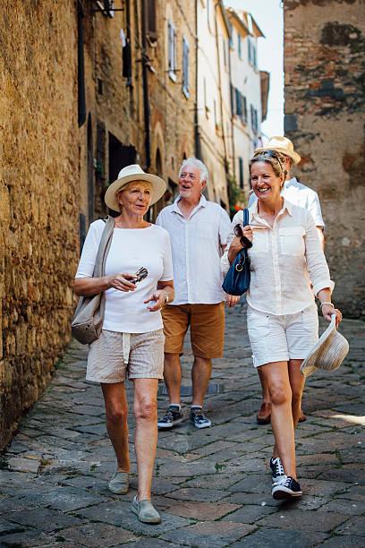 mature friends looking around old town italy - toskana ferien stock-fotos und bilder
