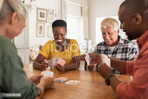 Retired multiethnic people playing cards together at home. Happy senior friends with african couple playing cards. Cheerful active seniors playing game at lunch table.