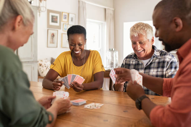Mature friends playing cards at home Retired multiethnic people playing cards together at home. Happy senior friends with african couple playing cards. Cheerful active seniors playing game at lunch table. playing card stock pictures, royalty-free photos & images