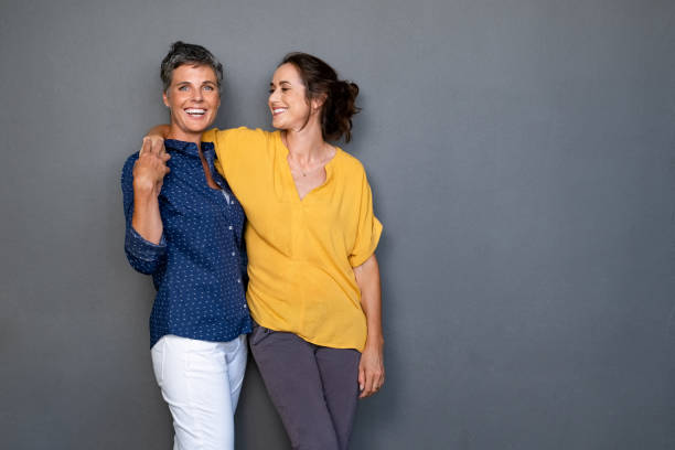 Mature friends women laughing together Mature happy women embracing each other against grey wall with copy space. Happy laughing ladies in smart casual standing on gray background. Cheerful middle aged woman with hand on shoulder of her stylish friend. two people stock pictures, royalty-free photos & images