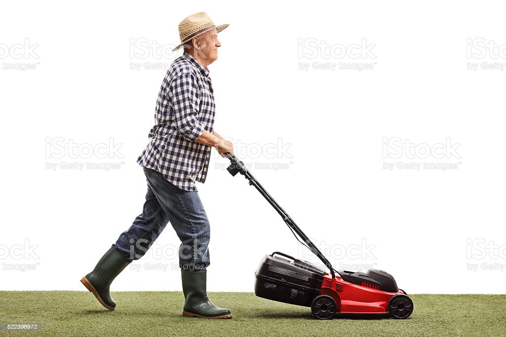 Mature gardener mowing a lawn stock photo