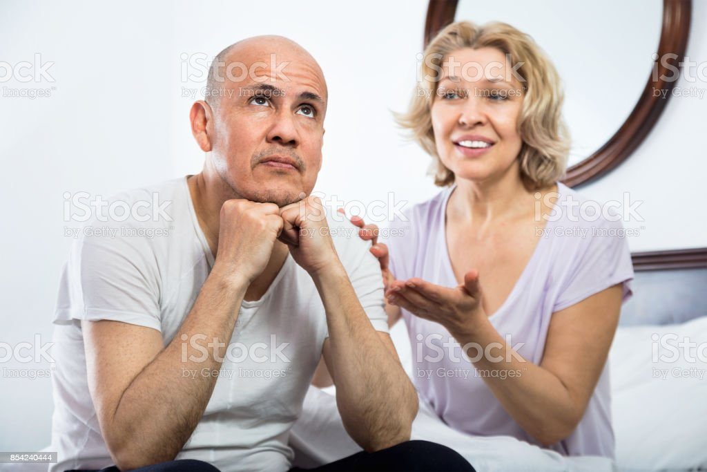 Mature  girlfriend consoling grieving man sitting apart stock photo