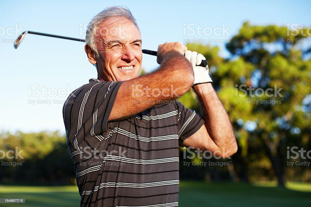 Mature golfer swinging stock photo