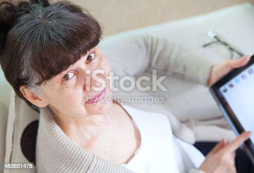 927814202 istock photo Mature good looking woman searching in internet on tablet device 483651478