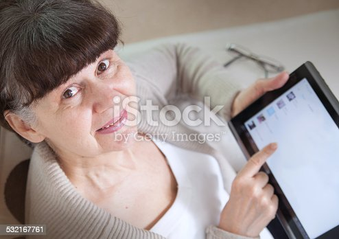 927814202 istock photo Mature good looking woman searching in internet on tablet device 532167761