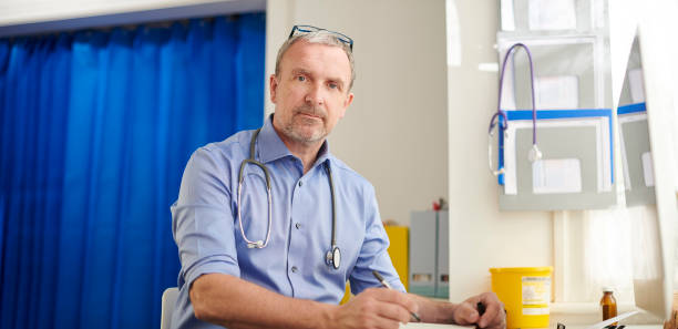 mature GP at his desk mature GP at his desk general practitioner stock pictures, royalty-free photos & images