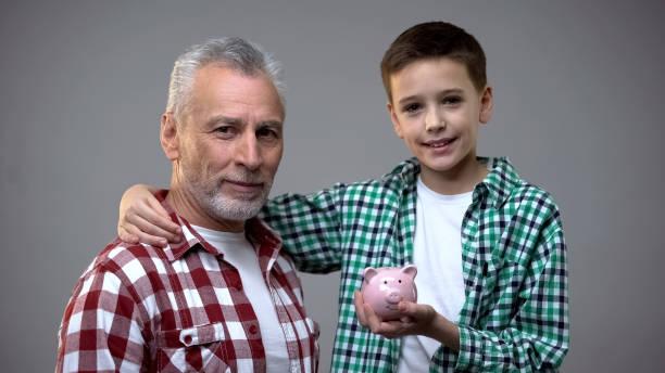 reife großvater und sein kleiner enkel blickend auf die kamera halten sparschwein - kindergeldantrag stock-fotos und bilder