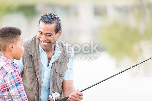 646011750 istock photo Mature grandfather helps grandson fish 619774366