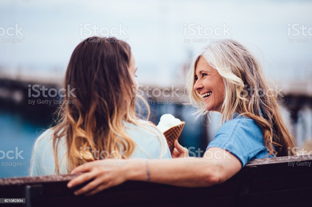 Mature grandmother and granddaughter eating ice-cream sitting on a bench stock photo