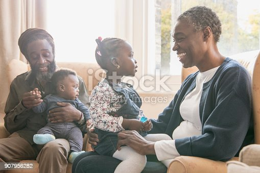 Grandfather sitting on armchair with grandson, grandmother smiling at granddaughter