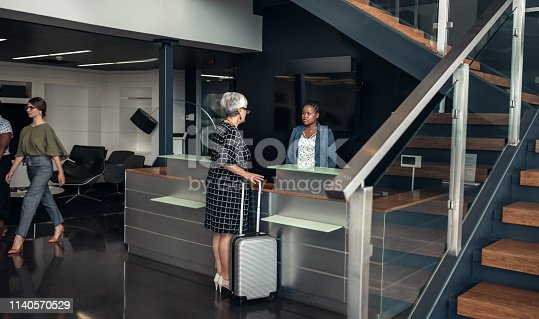 Mature grey haired business woman checking in to a modern hotel in a central business district