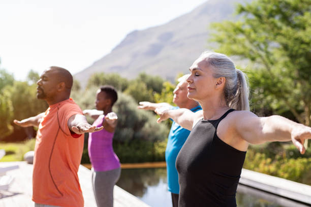 Mature group of people doing breathing exercise Group of senior people with closed eyes stretching arms outdoor. Happy mature people doing breathing exercise near pool. Yoga class with women and men doing breath exercise with outstretched arms. Balance and meditation concept. wellbeing stock pictures, royalty-free photos & images