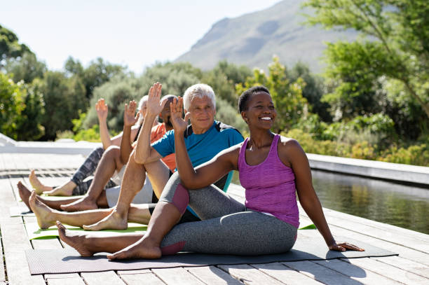 Mature group of people doing yoga exercise Senior men and mature women doing yoga exercise near swimming pool outdoor.Multiethnic people in a row practicing stretching exercise. Group of middle aged sporty people practicing pilates lesson. yoga class stock pictures, royalty-free photos & images