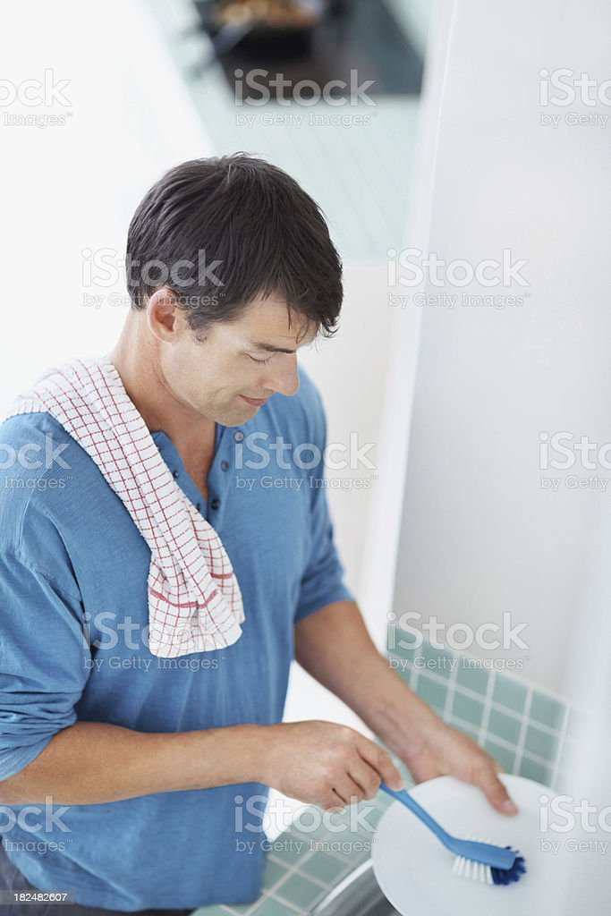 Mature guy cleaning plates in wash basin royalty-free stock photo