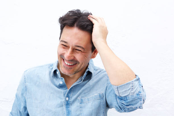 mature guy smiling with hand on head against white background stock photo