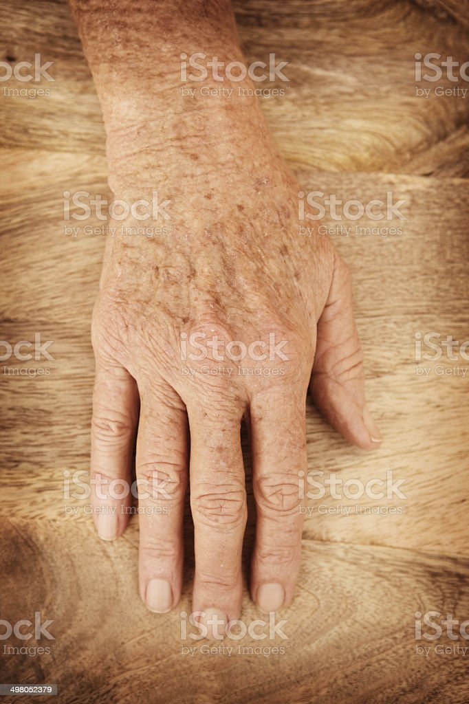 Mature hand on wooden background stock photo