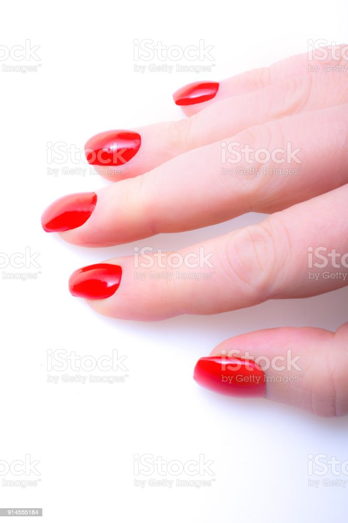 Close up Mature female hand with short red acrylic nails