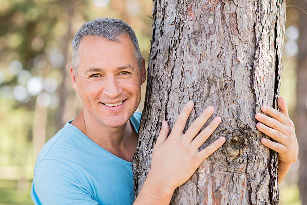 Mature handsome man hugging a tree Mature handsome man hugging a tree tree hugging stock pictures, royalty-free photos & images