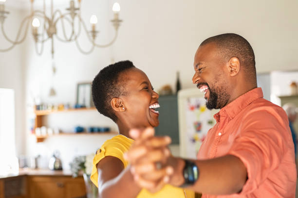 Mature happy couple dancing at home Cute mature couple dancing at home for their anniversary. Happy black woman enjoying a dance in the arms of her husband. Happy african couple dancing together in the kitchen and having fun together. husband stock pictures, royalty-free photos & images