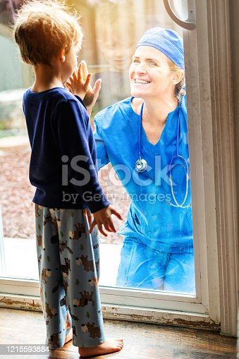 Caucasian Mature Healthcare worker posing seeing her son with a window glass separating them to avoid possible contagion