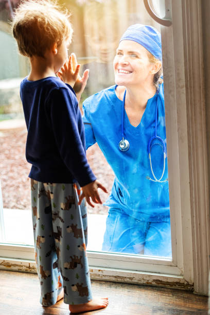 mature healthcare worker posing seeing her son with a window glass separating them to avoid possible contagion - hand on glass covid foto e immagini stock