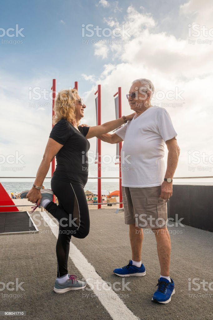 Mature heterosexual couple exercising together. Man supporting woman while she stretches her quadriceps stock photo