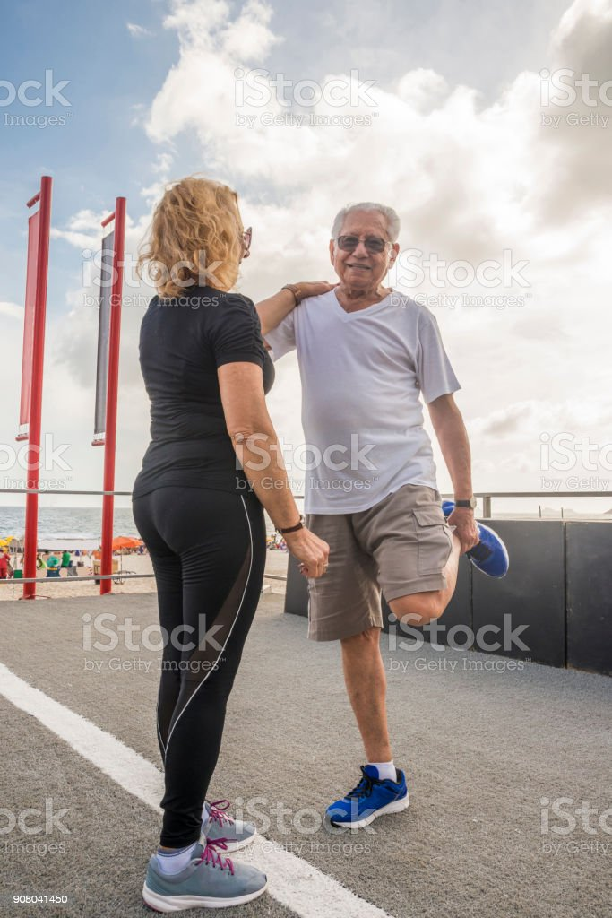 Mature heterosexual couple exercising together. Woman supporting man while stretching his quadriceps stock photo