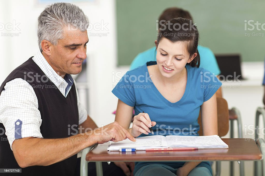 mature high school teacher helping student royalty-free stock photo