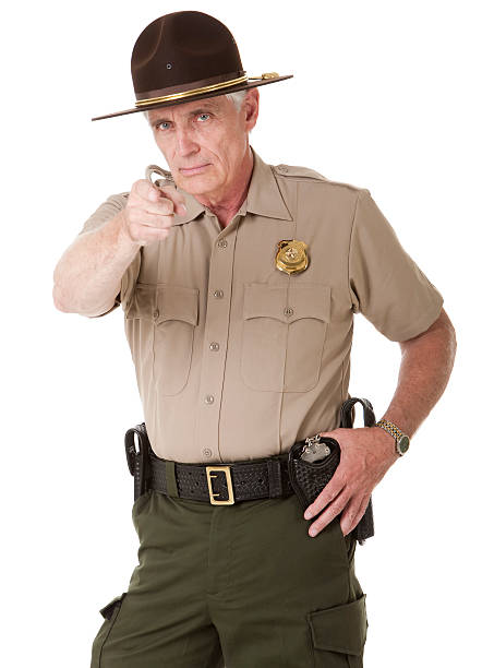 Mature Highway Patrolman Pointing Portrait of a mature male law enforcement officer (highway patrol, sheriff, or park ranger) pointing at the viewer. Isolated on a pure white background. park ranger stock pictures, royalty-free photos & images