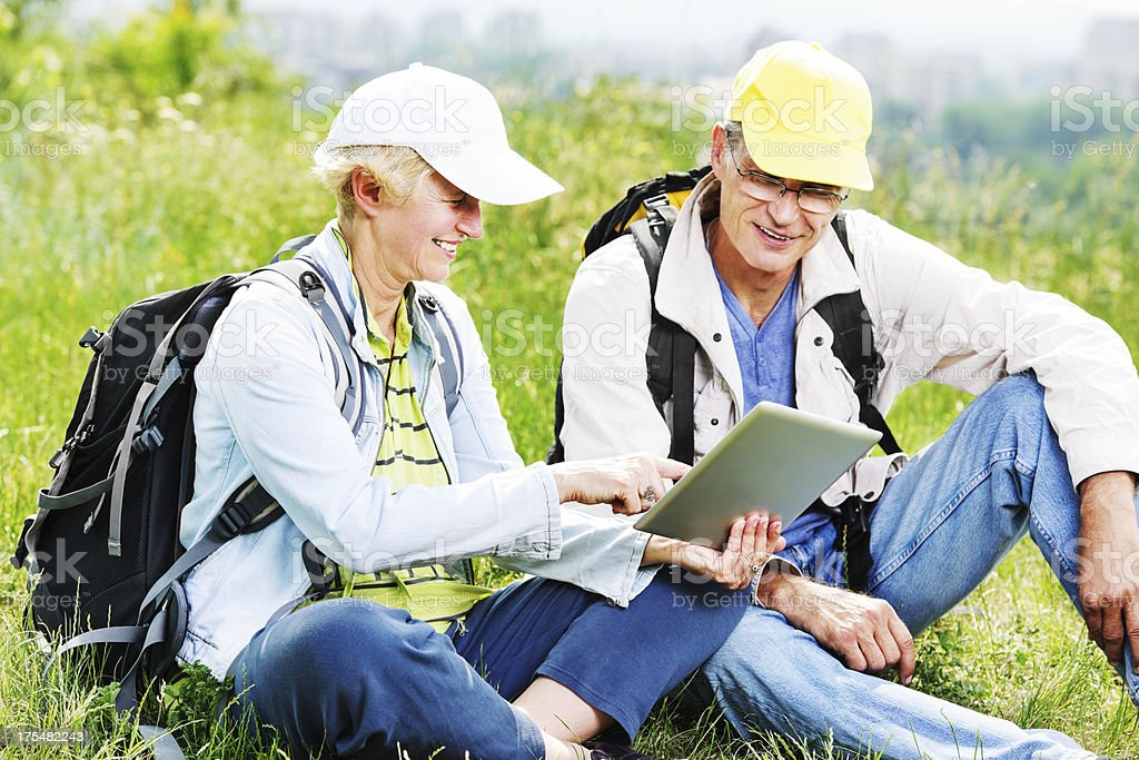 Mature hikers using digital tablet. royalty-free stock photo