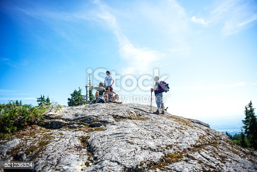 903015102 istock photo Mature Hikers Using Mobile Phone Navigation Application on Wilderness Mountaintop 521236324