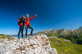 happy smiling sporty mature adult couple hikers mountaineers standing together on rocks high up in austrian mountains european  alps above timber line on sunny summer day with clear blue sky man pointing both looking in same dircetion