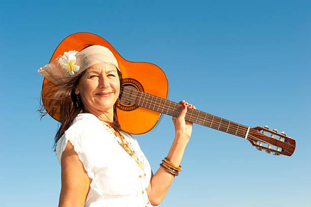 ältere hippie frau mit gitarre - hippie stirnbänder stock-fotos und bilder