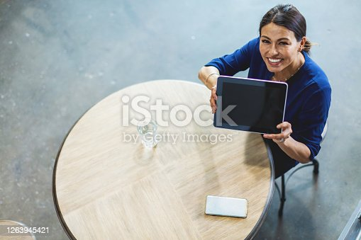 In Western Colorado Corporate Office Work Business and Commerce Using Technology Mature Adult Female of Hispanic Ethnicity with long black hair pulled back taken from high angle as second person point of view with subject sitting at round wood-top table on a cement floor while looking up at and holding digital tablet screen toward camera (Shot with Canon 5DS 50.6mp photos professionally retouched - Lightroom / Photoshop - original size 5792 x 8688 downsampled as needed for clarity and select focus used for dramatic effect)