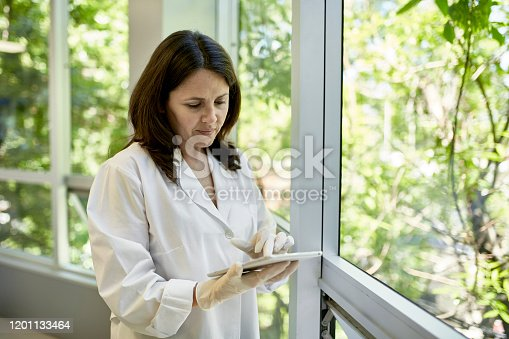 Close-up of Hispanic female pathologist in late 40s wearing lab coat and using digital tablet while standing next to lab window with view of lush foliage.