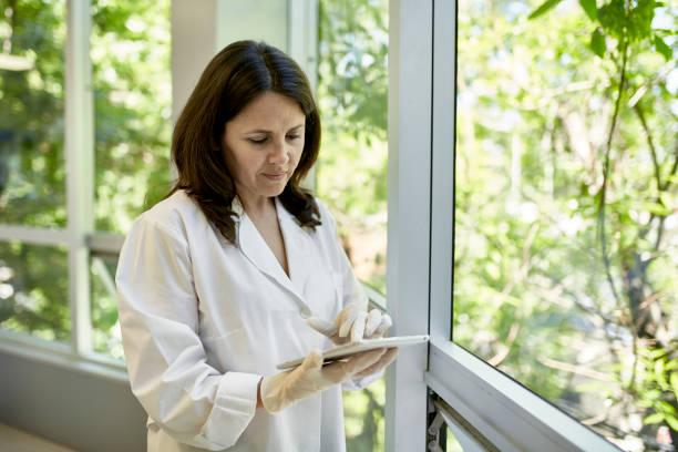 Reife hispanische pathologische Pathologin mit digitalen Tablet – Foto