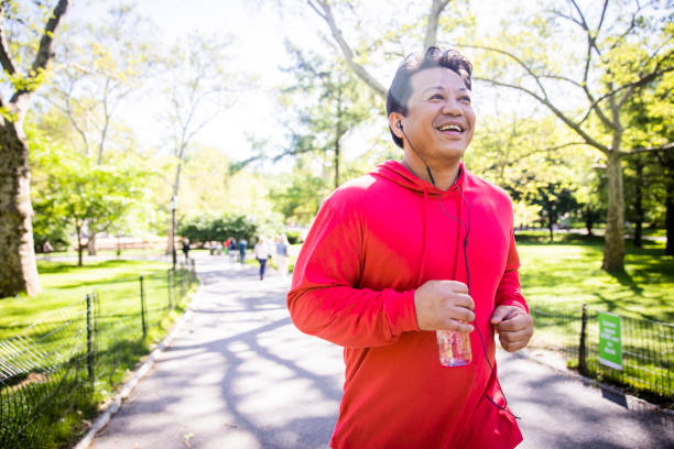 Mature Hispanic Man Jogging in Central Park A mature hispanic man working out in central park in New York City cardiovascular exercise stock pictures, royalty-free photos & images