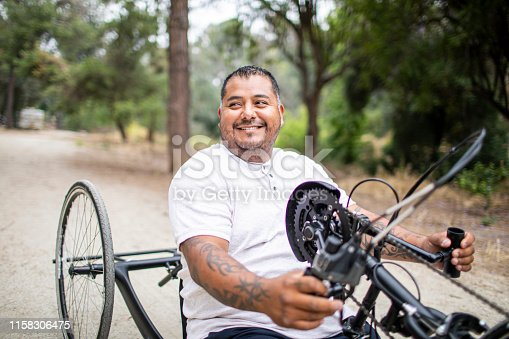 A mature hispanic man rides his handcycle. He is a double amputee.