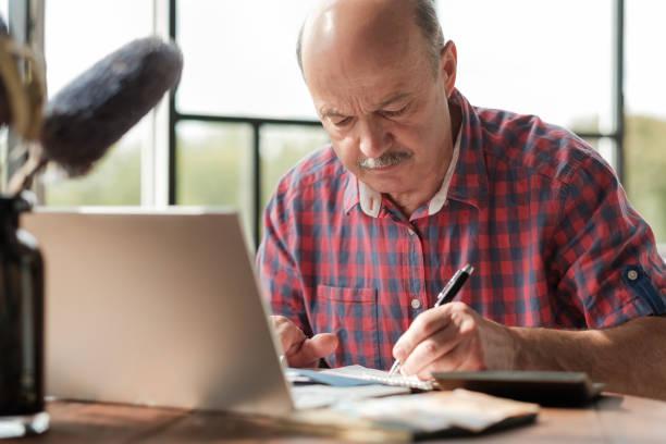 Mature hispanic man sitting at his desk and taking notes stock photo