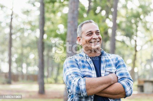 A mature Hispanic man in his 50s wearing a plaid shirt, standing in a park, smiling with his arms crossed.