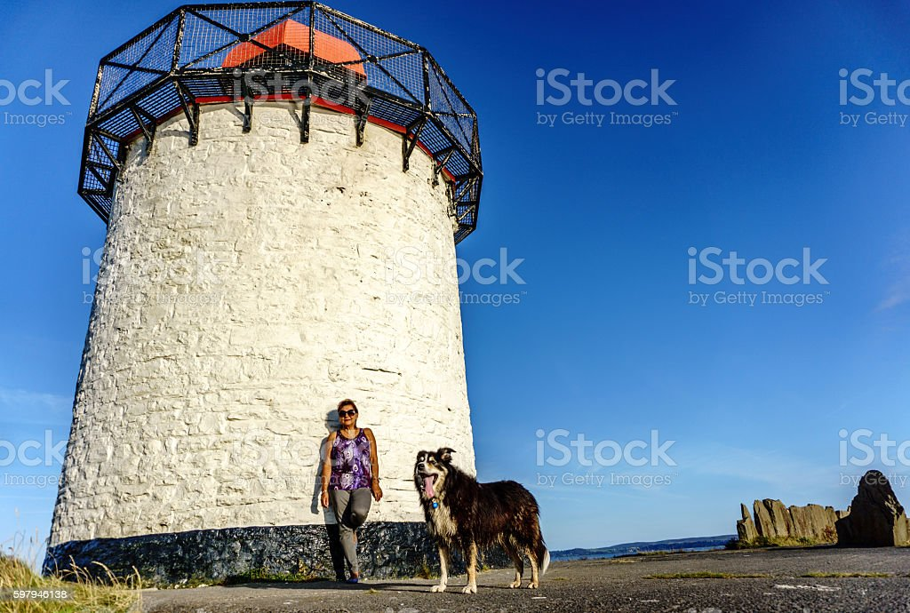 Mature hispanic woman and dog portrait by lighthouse foto royalty-free