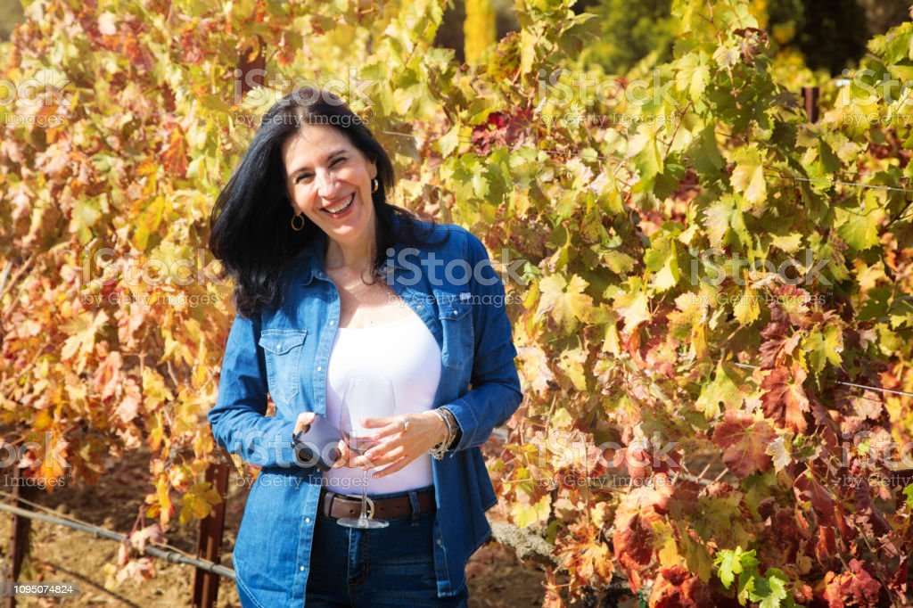 Mature Hispanic woman portrait laughing in vineyard at Autumn, mobile...