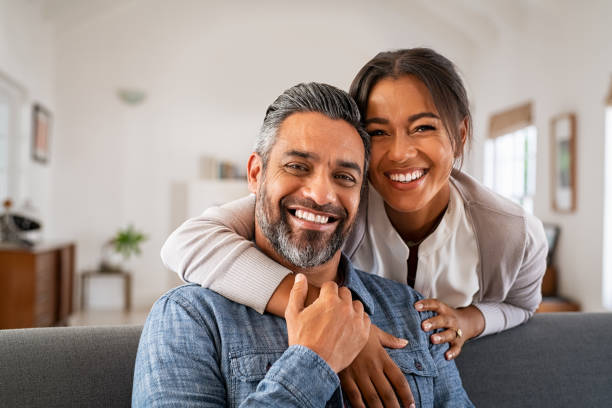 Mature indian couple hugging and looking at camera stock photo