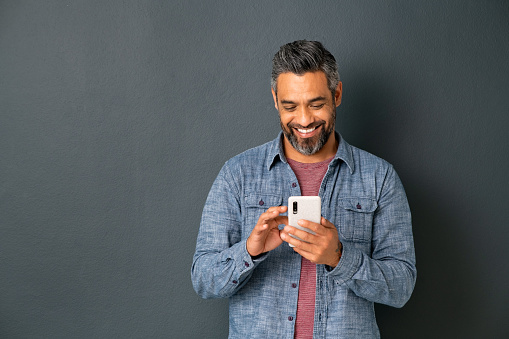 Mid adult multiethnic man texting phone message on smart phone isolated on grey background. Smiling middle eastern man using smartphone leaning on gray wall. Happy mixed race guy using new app on mobile phone with copy space.