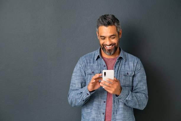 Mature indian man messaging on smartphone stock photo