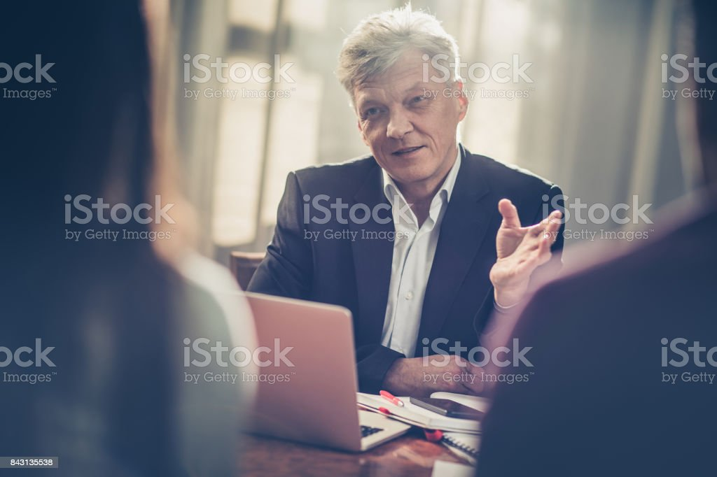 Mature insurance agent advising clients in the office. stock photo