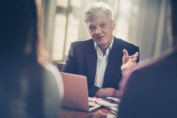 mature insurance agent advising clients in the office. - bankers stock photos and pictures