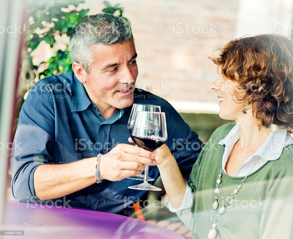 Mature Italian couple drinking wine in a cafe royalty-free stock photo